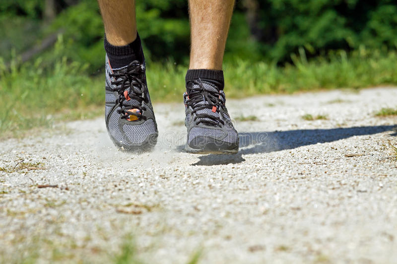 Trail running sport shoes in summer nature. Trail runner in summer nature, running closeup stock image