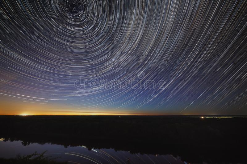 The trail of stars in the night sky is reflected in the river. Movement in space.  royalty free stock images