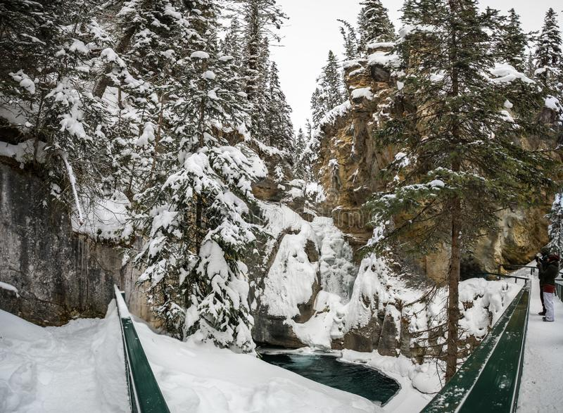 Johnston Canyon Lower falls during a frosty and snowy day, bow river, alberta Canada. The trail to the Lower Falls is fairly flat and smooth, initially through stock photo