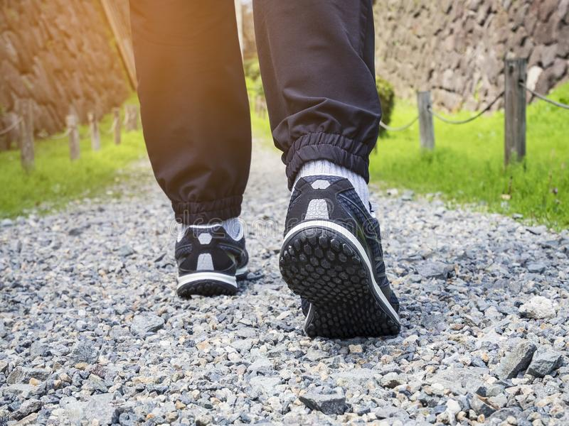 Trail walking Man legs with sport shoe Forest Park outdoor. Adventure lifestyle royalty free stock photography