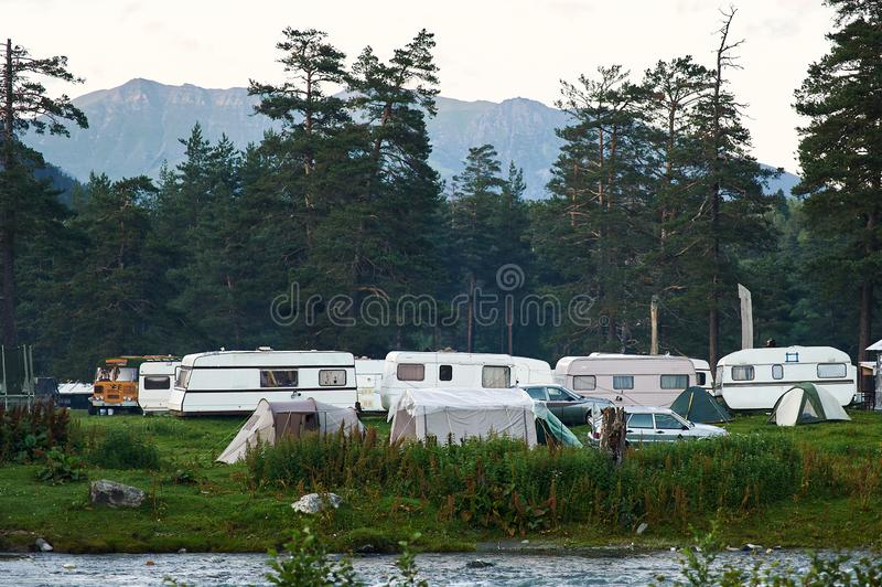 Trailer camp at green valley in the forest. glade full of camper vans.  stock photos
