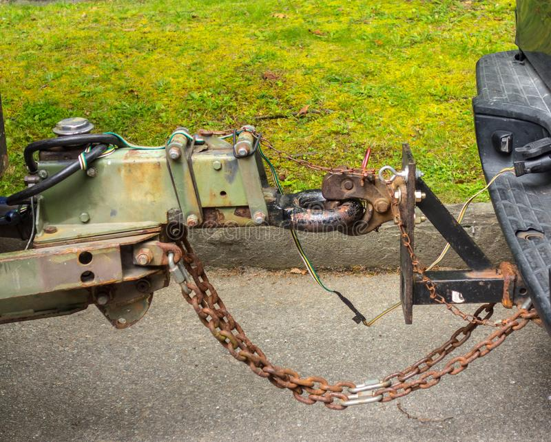 A trailer hitch with a rusting chain being used to join two vehicles together. A mechanism being used to safely pull a trailer behind a pick-up truck royalty free stock image