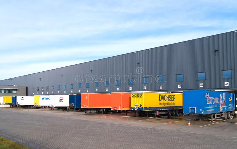 Trailers in front of warehouse. ALMELO, NETHERLANDS - FEBRUARY 4, 2017: Trailers in different colors in front of a large warehouse building stock image