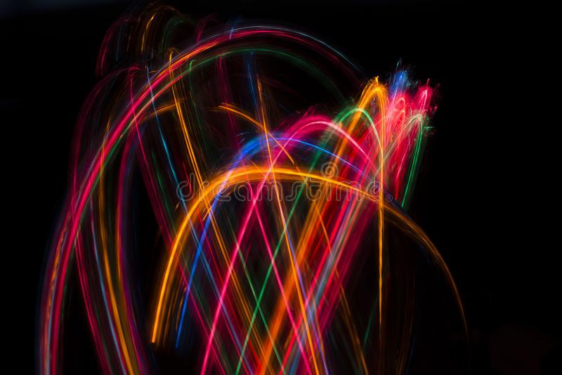 Trails of multicolored radial lights blurred on black. Can use background royalty free stock image