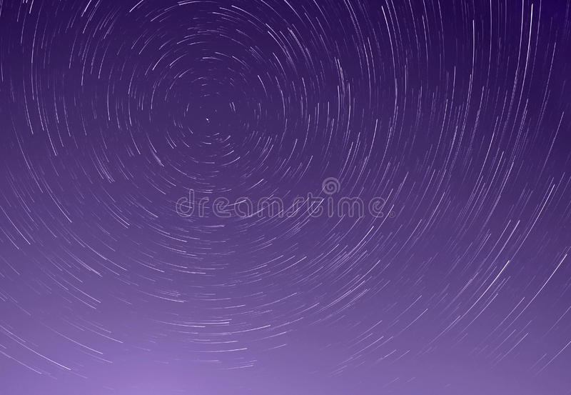 Trails of stars in sky stock image
