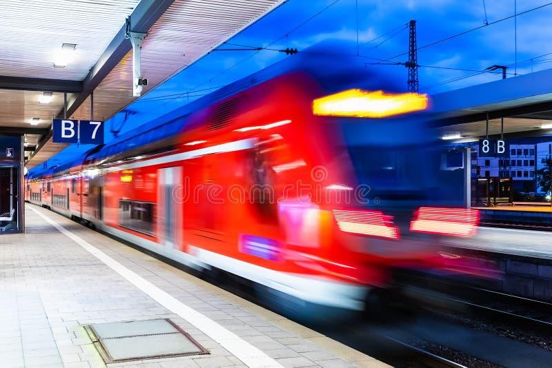 Train à grande vitesse à la plate-forme de gare ferroviaire la nuit photo stock