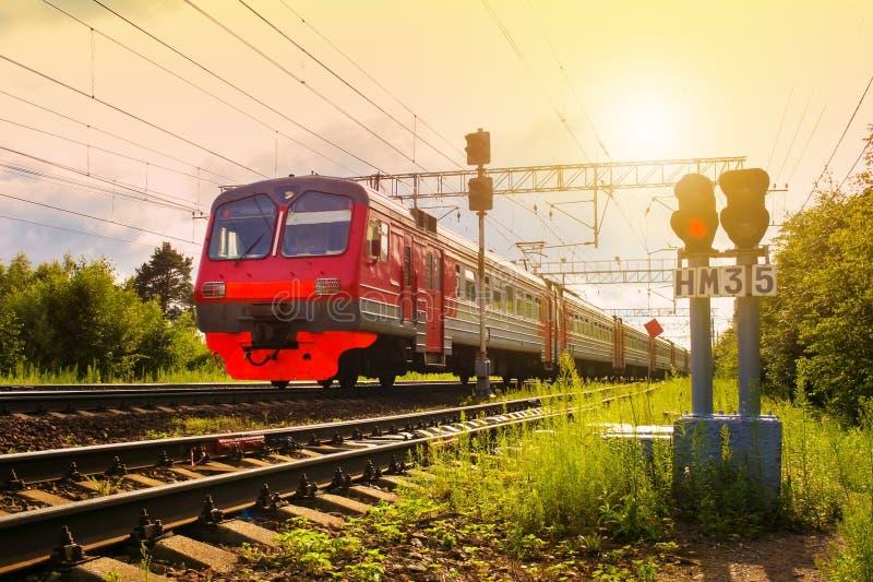 Train électrique de passager, se déplaçant contre un coucher du soleil et des feux de signalisation dans le premier plan photo stock