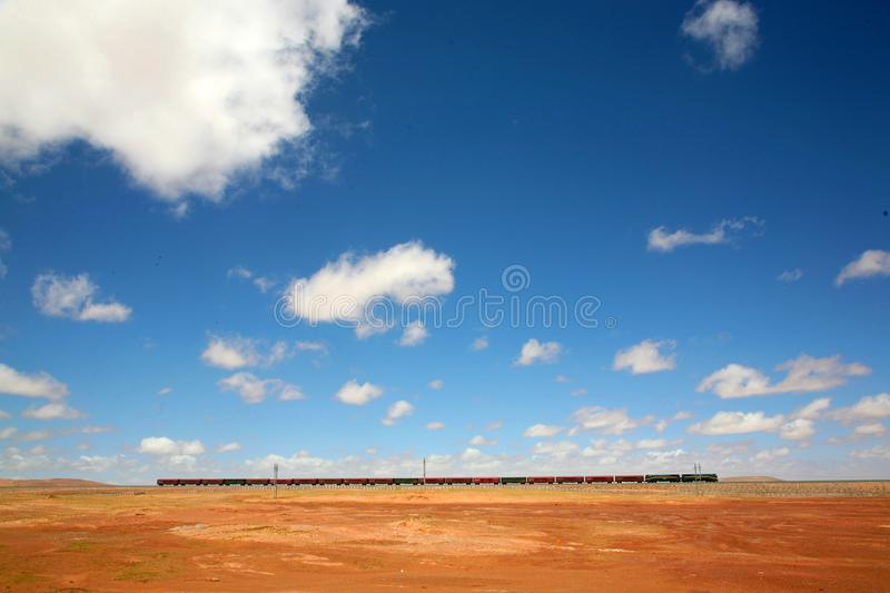 A train. A freight train is rumbling in the vast land, red and green railroad cars look so cute stock image