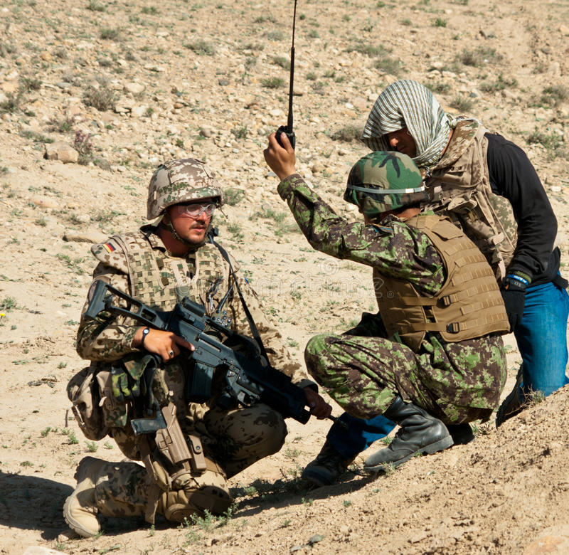 Train and Advise. German Army Officer and his interpreter working with a member of the Afghan National Army stock photography