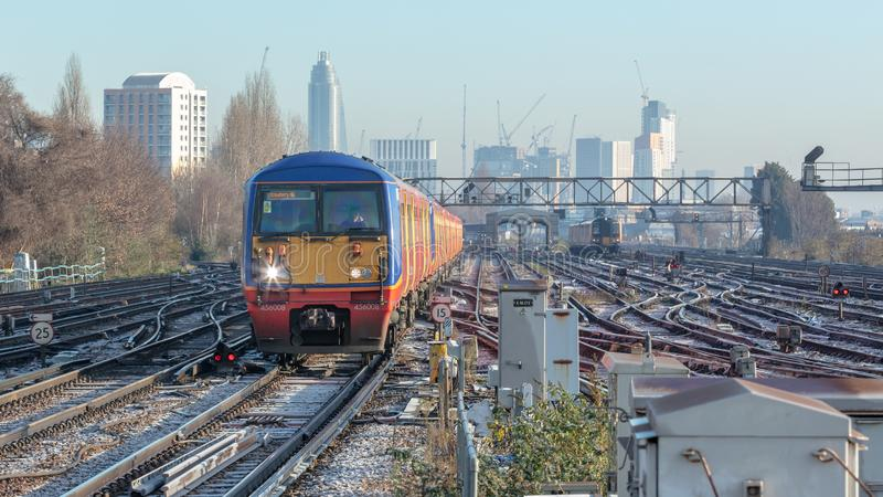 Train Approaches the Camera with London Skyline Behind stock photo