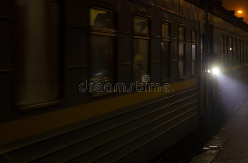The train arrives at the platform at night. Bright rays of light disperse the darkness. Background stock photo