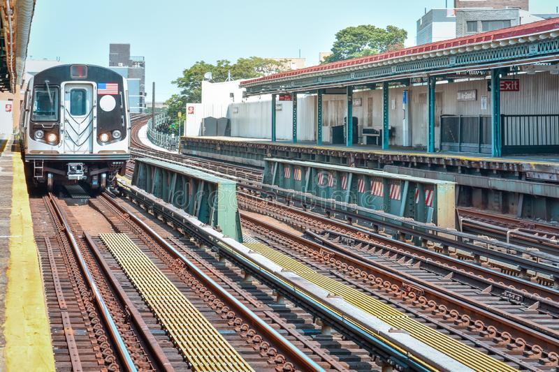 Train arriving at the station in New York City. Buildings in the background, cityscape. Travel and transit concept. Manhattan, NYC. USA royalty free stock image