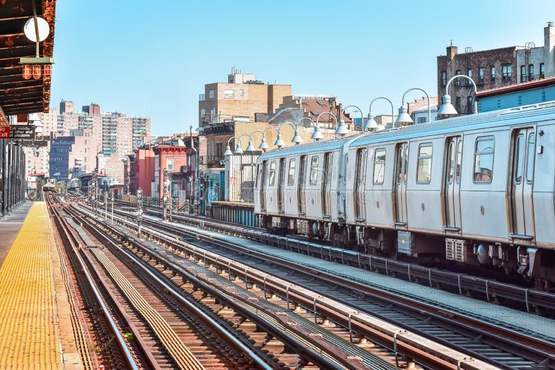 Train arriving at the station in New York City. Buildings in the background, cityscape. Travel and transit concept. Manhattan, NYC. USA royalty free stock photo
