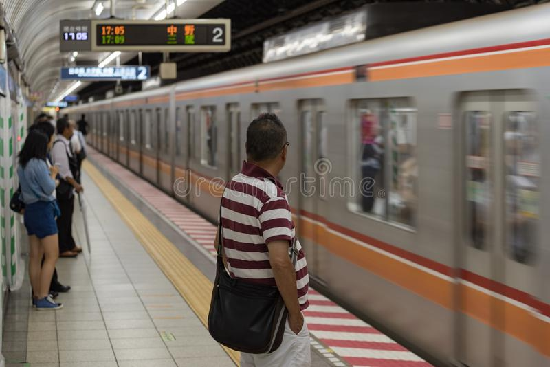 Train arriving at Tokyo Metro station with people waiting on the platform stock photos