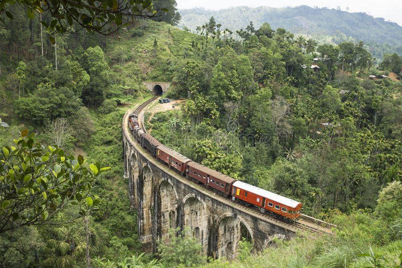 Train from the back in the mountains of Ella, Sri Lanka. Full train on a stone brigde in the jungle riding to a tunnel, Ella, Sri Lanka royalty free stock photo
