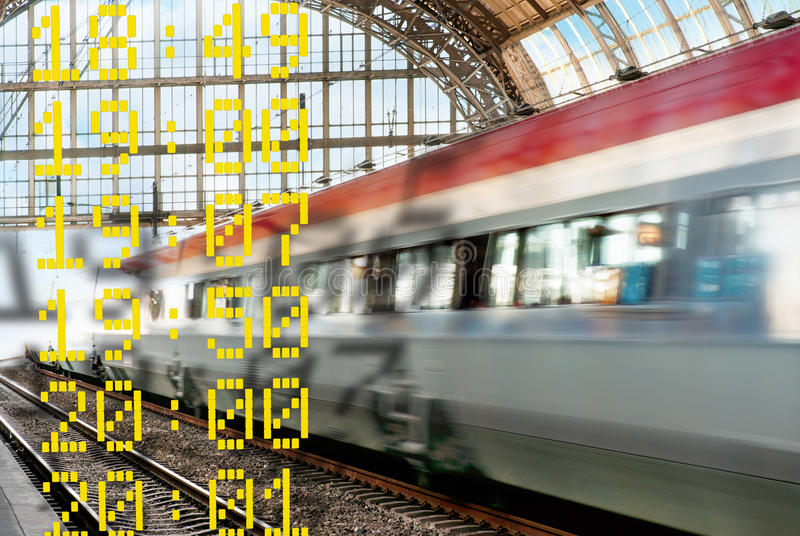 Train in blurred motion. Leaving a station, with departure times in foreground royalty free stock photos