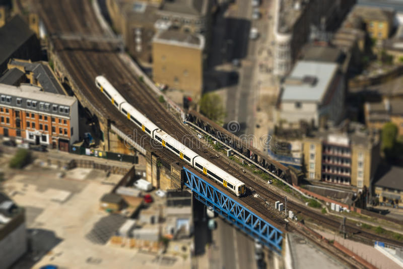 Train on a bridge in London, tilt-shift effect. Aerial view of a train on a bridge in London, tilt-shift effect, England, UK royalty free stock photo