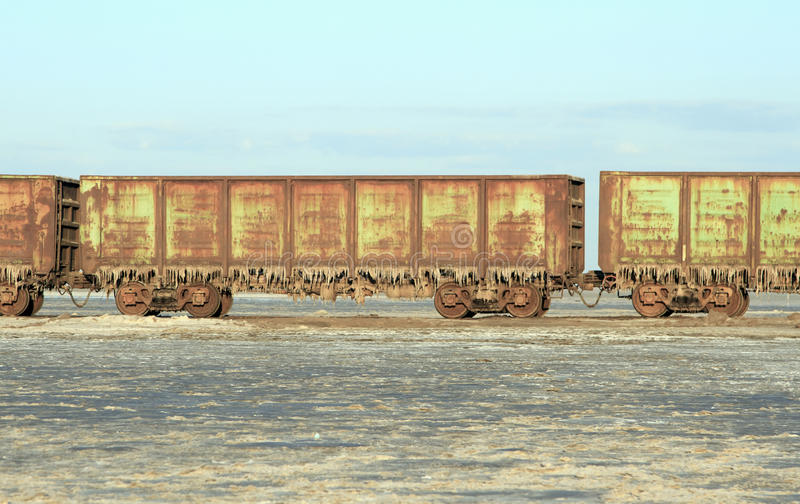 Train cars with stalactites of salt in the lake Baskun royalty free stock photo