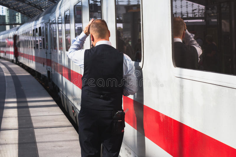 Train conductor from behind standing at station in front of train royalty free stock photos