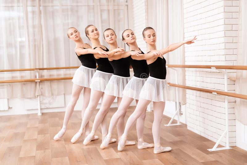 Girls ballet dancers rehearse in ballet class. They train dance moves. They use ballet barre. They are professional theater actors stock image