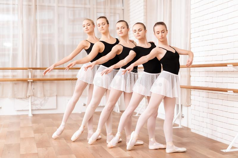 Girls ballet dancers rehearse in ballet class. They train dance moves. They use ballet barre. They are professional theater actors stock photo