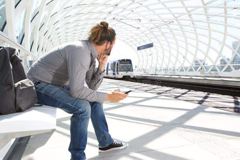 Train de attente d'homme arrivant à la station photographie stock