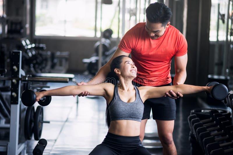 Train de couples de forme physique avec des haltères dans le gymnase photo stock