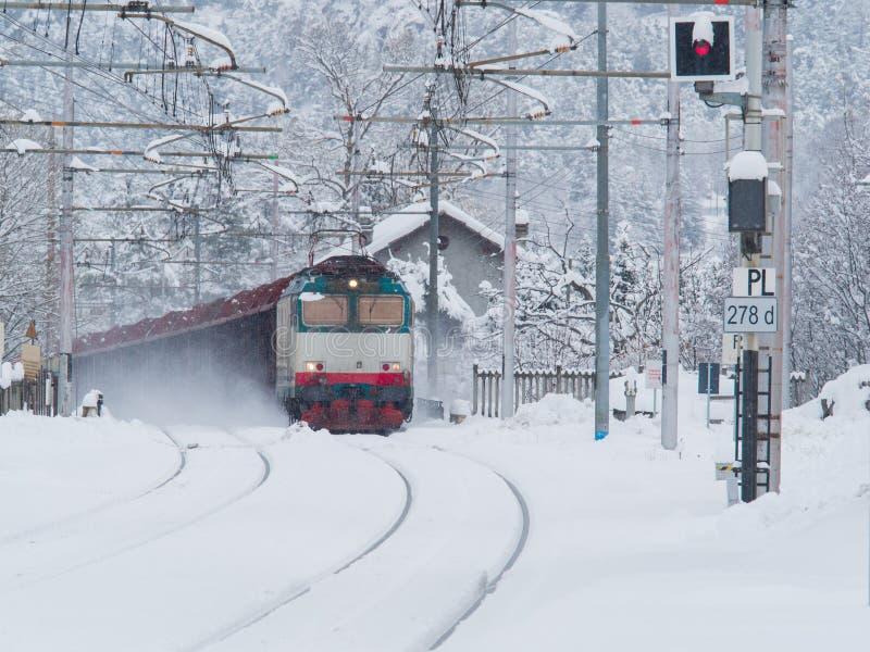 Train de fret fonctionnant sur les voies de chemin de fer tandis que neige image stock