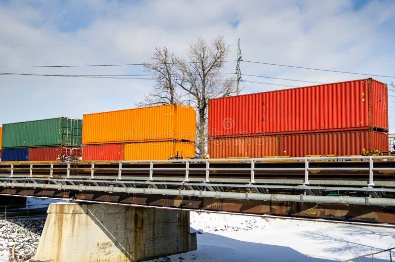 Train de fret passant au-dessus d'un pont de chemin de fer sur Sunny Winter Day photographie stock