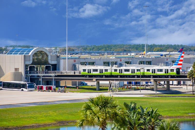 Train de petit pain-onroll- et vue partielle des avions chez Orlando International Airport 2 images stock