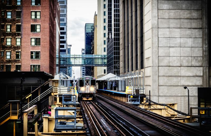 Train on elevated tracks within buildings at the Loop, Glass and Steel bridge between buildings - Chicago City Center - Vintage Da royalty free stock image
