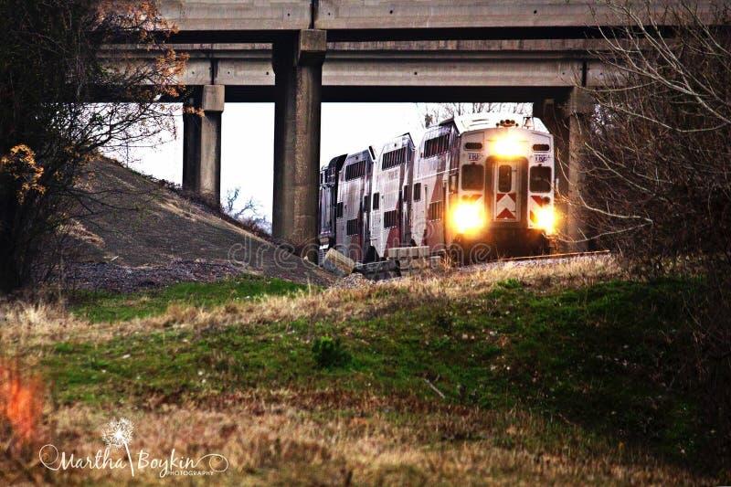 Train entering under bridge royalty free stock photography