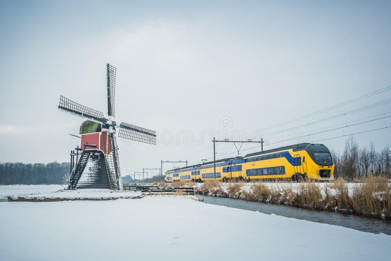 Train et moulin à vent de Néerlandais dans le paysage d'hiver photos libres de droits