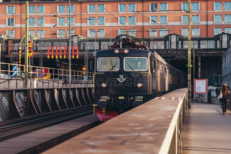 Train exiting the tunnel under Hilton hotel on its way to the Central Station. Editorial 27.03.2019 Stockholm Sweden. Train exiting the tunnel under Hilton hotel stock photography