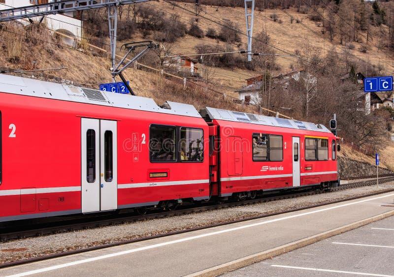 Train ferroviaire de Rhaetian quittant la gare ferroviaire de Filisur dans un commutateur photos stock