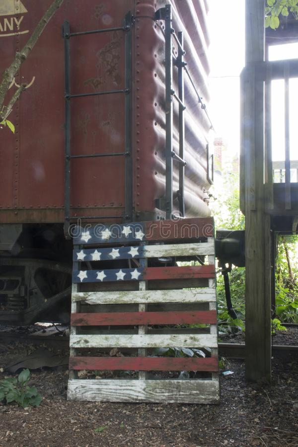 Train and flag decoration. An old railroad car and a pallet with the flag of the United States painted on it for decoration. the railroad cars have been retired stock image