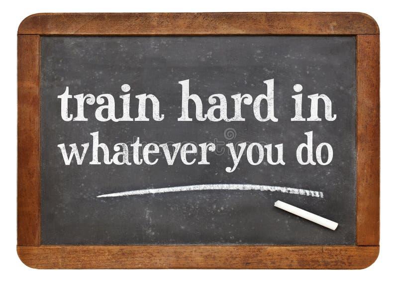 Train hard in whatever you do - blackboard sign. Train hard in whatever you do - advice in white chalk on a vintage slate blackboard stock photos