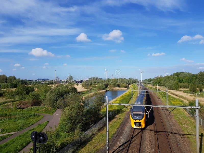 Train interurbain sur la voie de chemin de fer avec des turbines de compensation et de vent de nature produisant l'énergie verte photo libre de droits