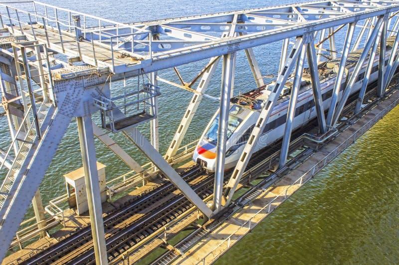 Train moderne dévalant à travers le pont au-dessus de la rivière photo stock
