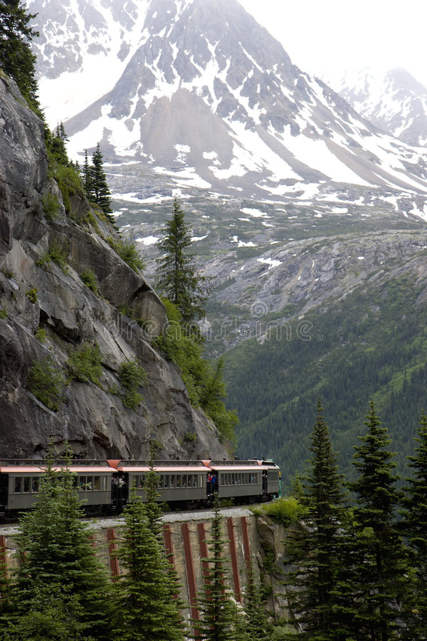 Train in mountains. Train passes through mountains near Canada / US border, Alaska in the White Pass royalty free stock images