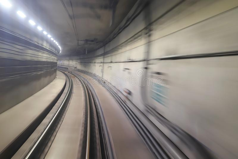 Train moving rail tunnel with moderate motion blur. Train moving in city rail tunnel with moderate motion blur stock photography