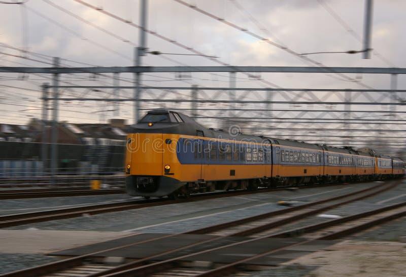 Train ou interurbain jaune conduisant très rapide avec la tache floue de mouvement, papier peint scénique photo libre de droits