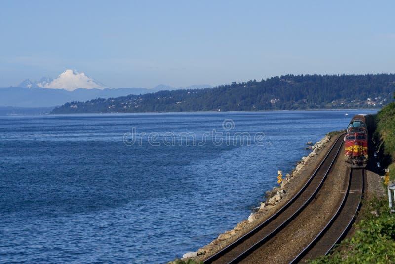 Train By Pacific Ocean Mount Baker. Train on Tracks Going By Pacific Ocean, Mount Baker in Background Edmonds, Washington, Northwest royalty free stock image
