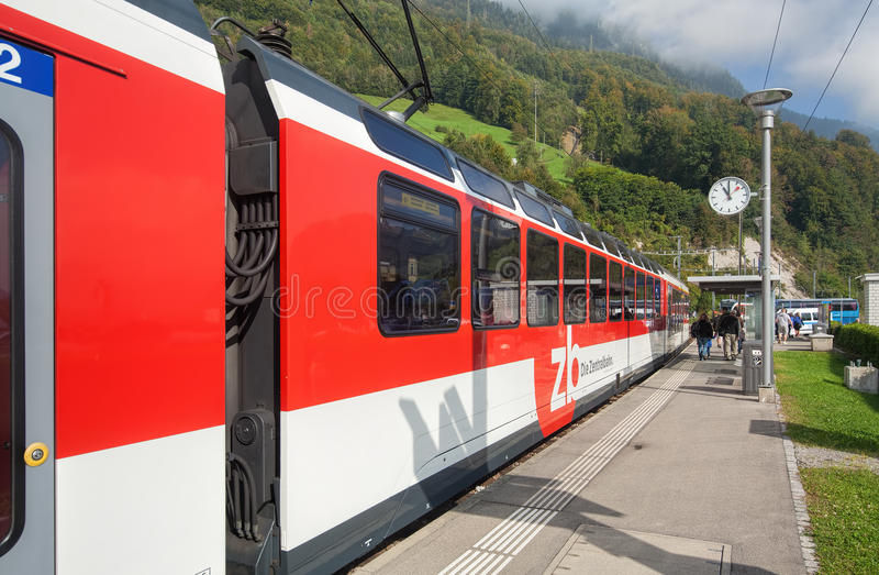 Train passing the Alpnachstad station. Alpnachstad, Switzerland - 23 September, 2014: a Zentralbahn train passing the Alpnachstad railway station. Zentralbahn is royalty free stock image