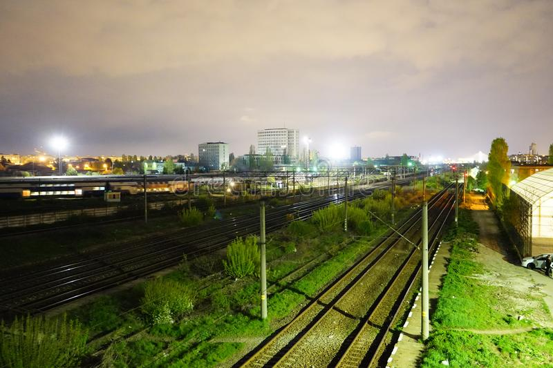 Night scene of rails and train in Carpati station, Bucharest, CFR. Train passing Carpati station in Bucharest Romania nightscene royalty free stock images