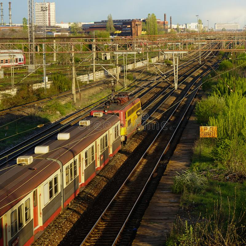 Rails and train in Carpati station, Bucharest, CFR. Train passing Carpati station in Bucharest Romania at sunset, view of the city in the background stock image