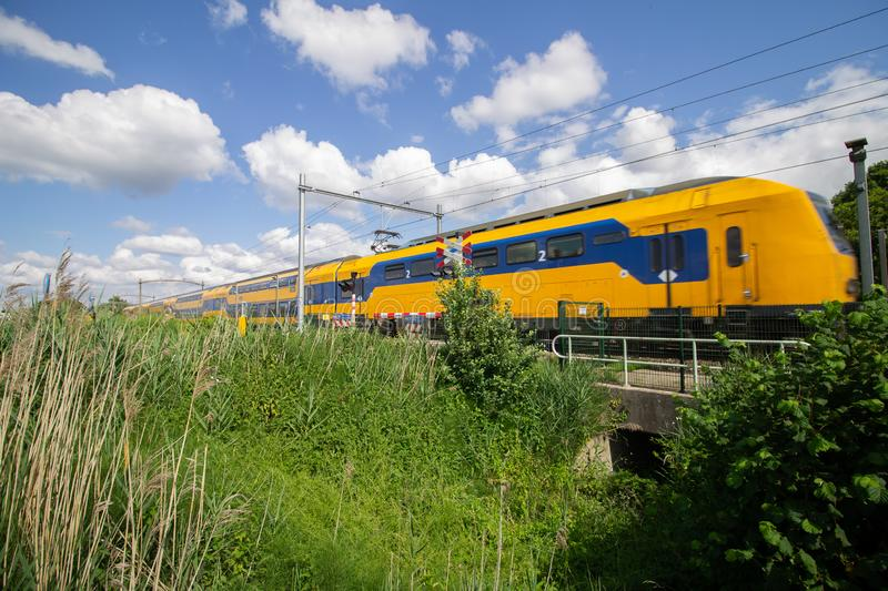 Train passing a level crossing at a sunny day with some clouds stock photography
