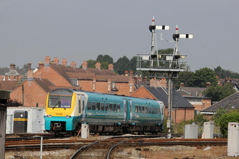 Train passing signal gantry at Shrewsbury station. Class 175 two car Coradia diesel multiple unit in Arriva Trains Wales livery leaving Shrewsbury railway royalty free stock image