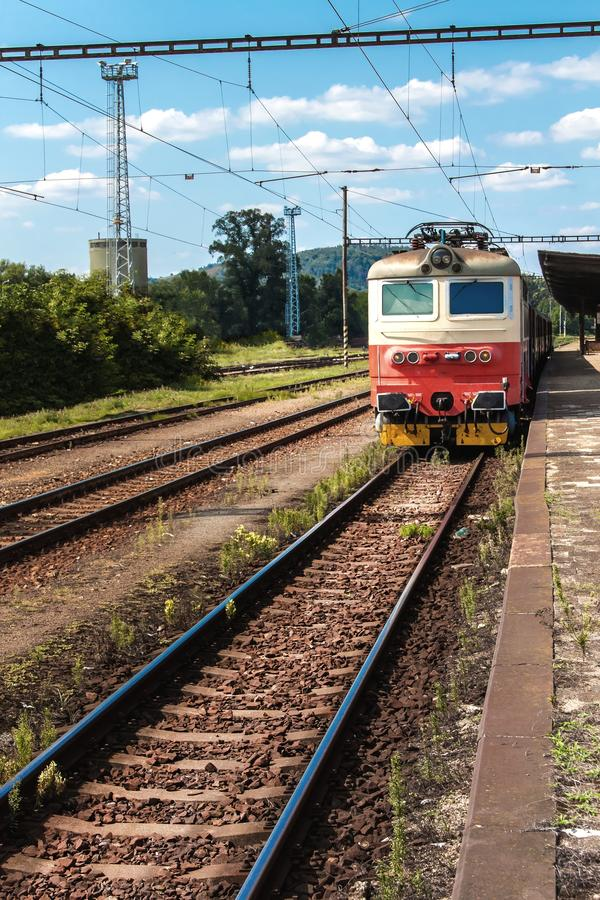 Train on platform in station in Czech Republic. Railroad tracks with concrete sleepers. Local railway station royalty free stock photos