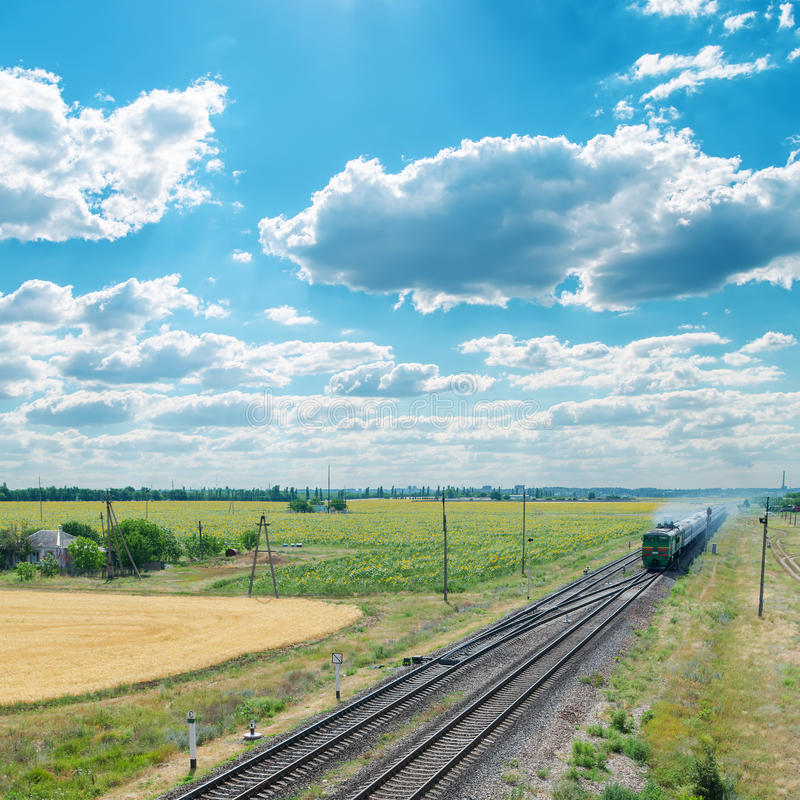 Train on railroad under cloudy sky royalty free stock images